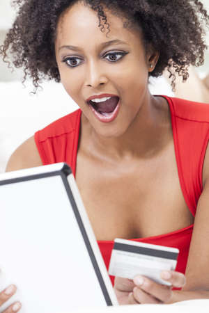 shopping card: A beautiful, happy and surprised, mixed race African American girl or young woman laying down wearing a red dress using a tablet computer and credit card internet shopping on line Stock Photo