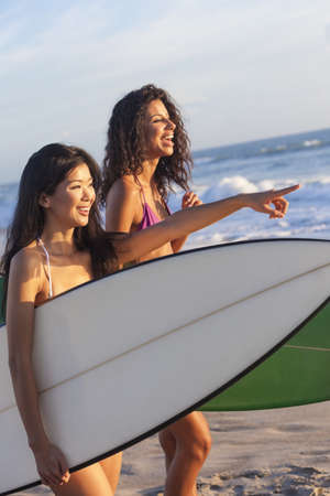 latina female: Beautiful young women surfer girls in bikinis with surfboards on a beach at sunset or sunrise