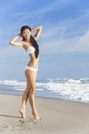 A beautiful Chinese Asian young woman or girl wearing a white bikini on an empty deserted tropical beach with a blue sky  Stock Photo - 15691414