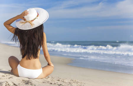 view from behind: A sexy young brunette woman or girl wearing a white bikini and sun hat sitting on a deserted tropical beach with a blue sky