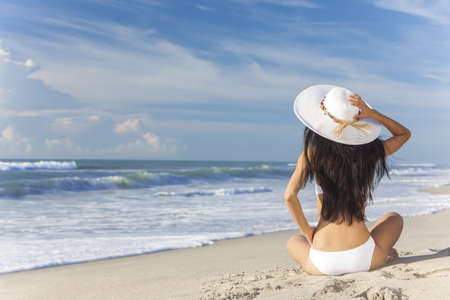 A sexy young brunette woman or girl wearing a white bikini and sun hat sitting on a deserted tropical beach with a blue sky  photo