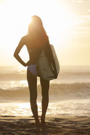 Rear view of beautiful sexy young woman surfer girl in bikini with white surfboard on a beach at sunset or sunrise Stock Photo - 15691411