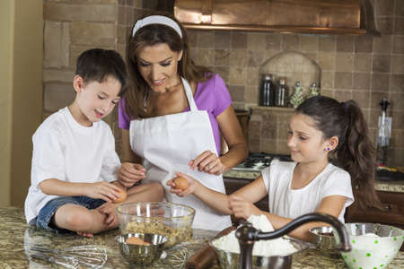 An attractive smiling family of mother, two children, girl, boy, son & daughter, breaking eggs & baking in a kitchen at home Stock Photo - 15691419