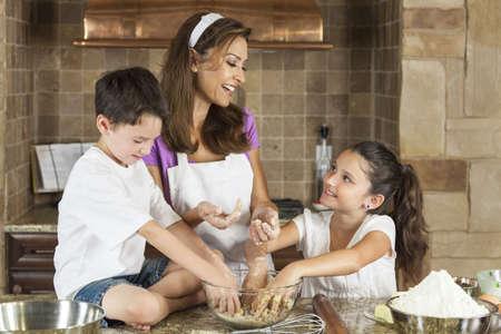 niños cocinando: Una familia sonriente atractivo de la madre y dos niños, niño, niña, hijo, hija hornear y comer galletas con chispas de chocolate en una cocina en casa