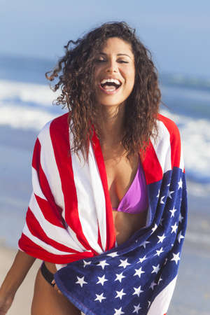 Beautiful young woman laughing wearing bikini and wrapped in American flag towel on a sunny beach Stock Photo - 15691420