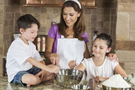 An attractive smiling family of mother and two children, girl boy, son daughter, baking in a kitchen at home Standard-Bild