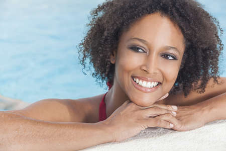 teeth white: A beautiful sexy young African American girl or young woman wearing a bikini and relaxing on the side of a swimming pool. Stock Photo