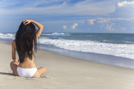 A sexy young brunette woman or girl wearing a white bikini sitting on a deserted tropical beach with a blue sky  photo