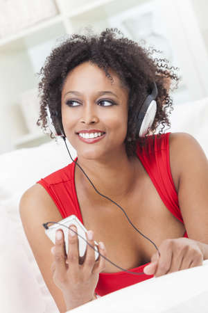 A beautiful mixed race African American girl or young woman laying down wearing a red dress listening to music on mp3 player and headphones photo