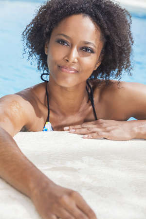 A beautiful sexy young African American girl or young woman wearing a bikini and relaxing on the side of a swimming pool  photo