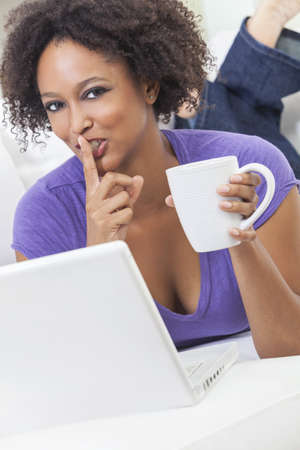 A beautiful happy mixed race African American girl or young woman laying down on sofa using a laptop computer drinking coffee   holding finger to her lips