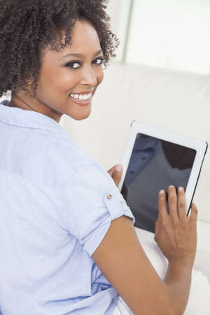 Beautiful happy young African American woman or girl smiling and using a tablet computer at home on her sofa Stock Photo