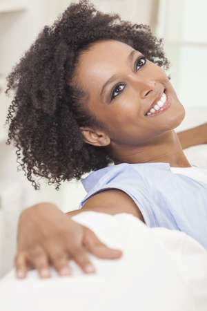 settee: A beautiful mixed race African American girl or young woman sitting on sofa at home looking happy and relaxed Stock Photo