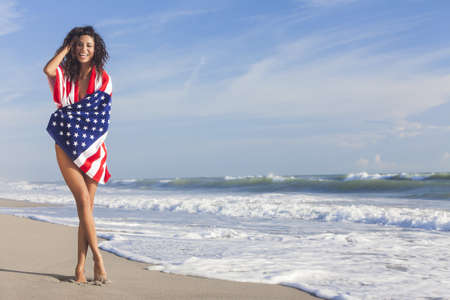 Beautiful young woman laughing wearing bikini and wrapped in American flag towel on a sunny beach Standard-Bild