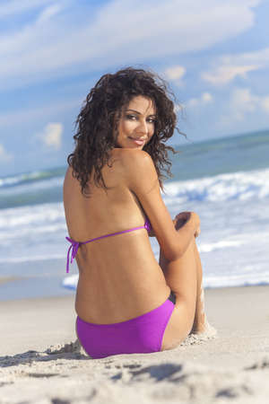 A sexy young brunette woman or girl wearing a purple bikini and sitting on a deserted tropical beach with a blue sky