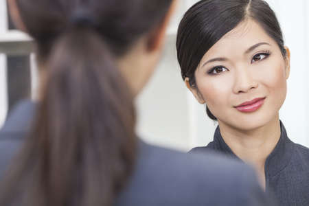 Portrait of a beautiful young Asian Chinese woman or businesswoman in office meeting with female colleague Stock Photo - 15941670