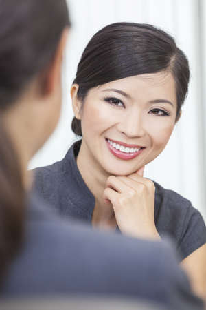 Portrait of a beautiful young Asian Chinese woman or businesswoman in office meeting with female colleague photo