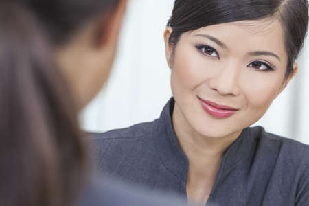 Portrait of a beautiful young Asian Chinese woman or businesswoman in office meeting with female colleague Stock Photo