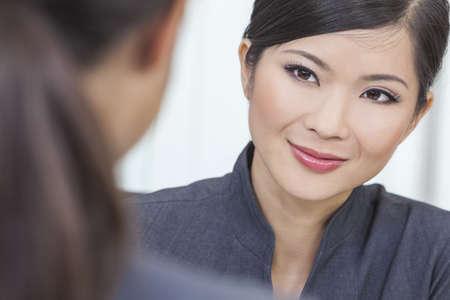 mujer china: Retrato de una joven y bella mujer asi�tica china o empresaria en oficina reuni�n con su colega femenina