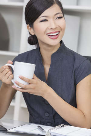 Beautiful young CChinese Asian woman businesswoman smiling, relaxing and drinking a cup of coffee or tea in her office Stock Photo - 15941674