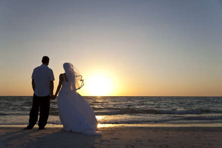 Wedding of a married couple, bride and groom, together at sunset on a beautiful tropical beach Stock Photo - 15941666