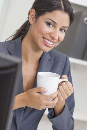 Beautiful young Latina Hispanic woman or businesswoman in smart business suit sitting at a desk drinking coffee in an office  photo