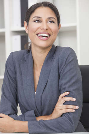 Beautiful happy young Latina Hispanic woman or businesswoman in smart business suit sitting at a desk in an office laughing photo