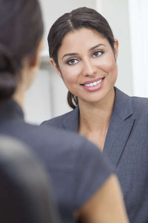 Beautiful young Latina Hispanic woman or businesswoman in smart business suit sitting at a desk in an office having a meeting with colleague photo