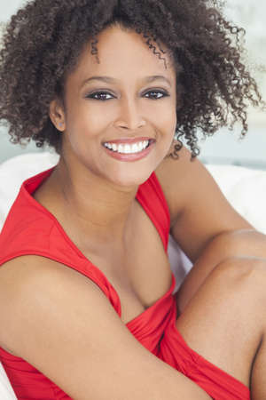 A beautiful mixed race African American girl or young woman lwearing a red dress looking happy and smiling Standard-Bild