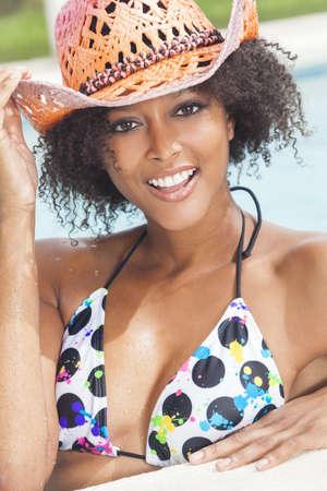 Una hermosa sexy joven mujer afroamericana ni�a o joven que llevaba un sombrero vaquero de paja bikini y riendo en la cara de una piscina