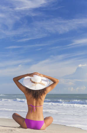 A sexy young brunette woman or girl wearing a bikini and sun hat sitting on a deserted tropical beach with a blue sky Stock Photo - 16299846