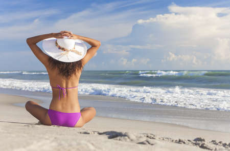woman back: A sexy young brunette woman or girl wearing a bikini and sun hat sitting on a deserted tropical beach with a blue sky