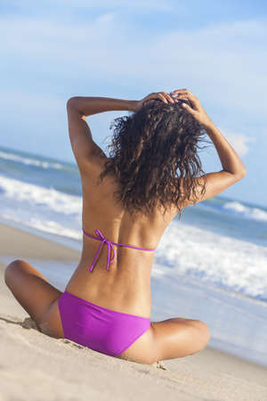 A sexy young brunette woman or girl wearing a purple bikini sitting on a deserted tropical beach with a blue sky  photo