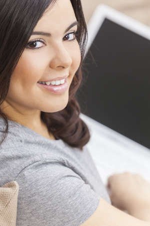 Beautiful happy young Latina Hispanic woman smiling and using a laptop computer at home on her sofa Stock Photo - 16484099