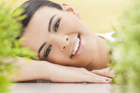 Health spa nature concept studio portrait of a beautiful young woman or girl resting on her hands smiling through natural green leaves Stock Photo - 16484084