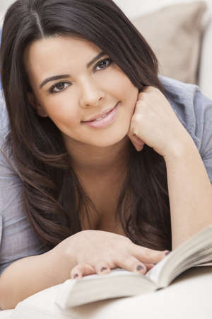 Beautiful happy young Latina Hispanic woman laying down reading a paperback book at home on her sofa Stock Photo - 16484175