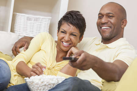 A happy African American man and woman couple in their thirties sitting at home, eating popcorn and using remote control watching a movie or television