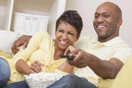 African American: Un feliz hombre afroamericano y mujer pareja de treinta�eros que se sienta como en casa, comiendo palomitas de ma�z y utilizar el control remoto viendo una pel�cula o la televisi�n