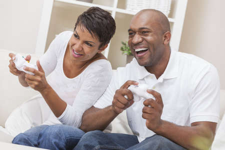 sexes: African American couple, man and woman, having fun playing video console games together