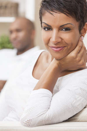 A happy African American man and woman couple in their thirties sitting at home, the woman is in focus in the foreground the man out of focus in the background Stock Photo - 16468147