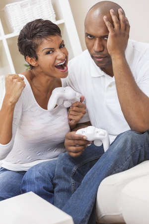 African American couple, man and woman, having fun playing video console games together  The woman has just beaten the man, she is celebrating, he is miserable  photo