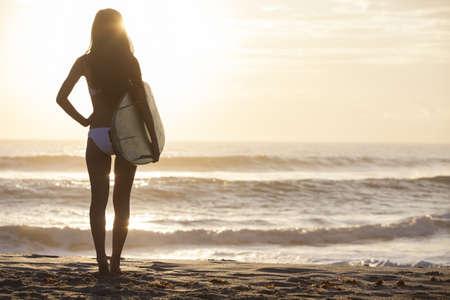 일출 또는 일몰에 해변에 흰색 서핑 보드와 비키니에서 아름 다운 섹시 한 젊은 여자 서퍼 소녀의 후면보기 스톡 콘텐츠
