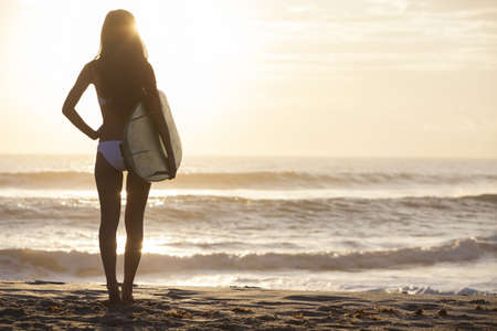 woman behind: Rear view of beautiful sexy young woman surfer girl in bikini with white surfboard on a beach at sunset or sunrise
