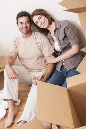 Happy couple in their thirties unpacking or packing boxes and moving into a new home Stock Photo - 16468149