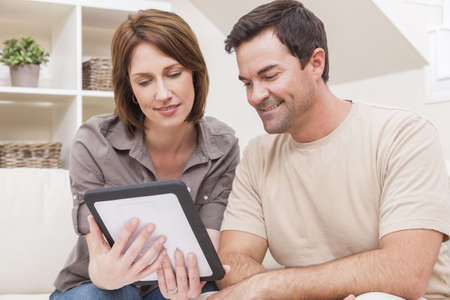 Happy man and woman couple in their thirties, sitting together at home on a sofa using a tablet computer