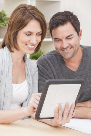 Happy man and woman couple in their thirties, sitting together at home by a table using a tablet computer Stock Photo - 16484174