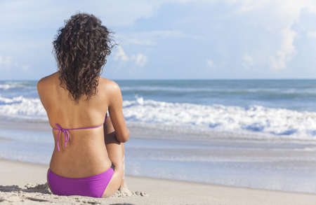 Rear view of a sexy young brunette woman or girl wearing a bikini sitting on a deserted tropical beach with a blue sky  photo