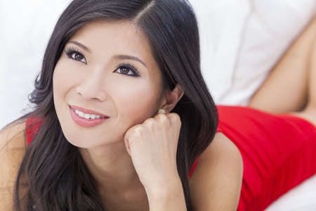 sexy asian woman: Portrait of a beautiful young Chinese Asian Oriental woman wearing a red dress resting on her hand