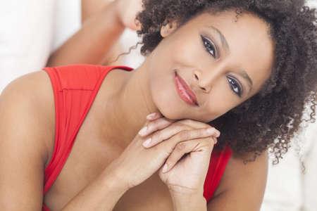 sch�ne frauen: Eine sch�ne Mischlinge African American M�dchen oder eine junge Frau, die Verlegung auf dem Sofa tr�gt ein rotes Kleid suchen gl�cklich