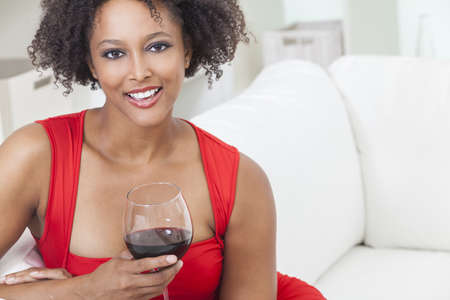 A beautiful mixed race African American girl or young woman wearing a red dress looking happy and drinking red wine Stock Photo - 16782652